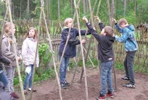 Kinder setzen Stangengerüst für Bohnen